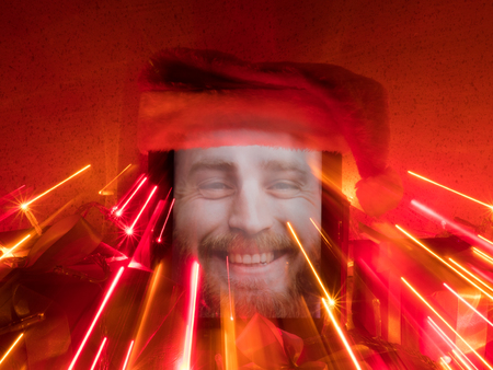 tablet with happy bearded male on screen and santa cap on it with Christmas attributes with lines painted with light