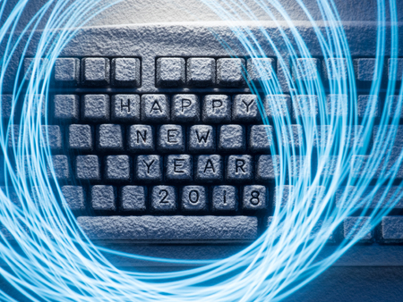 keyboard covered with snow with inscription happy new year 2018 with painted with light lines Stockfoto