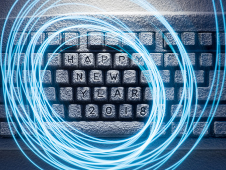 keyboard illuminated by light with circles painted by light with the inscription happy new year 2018