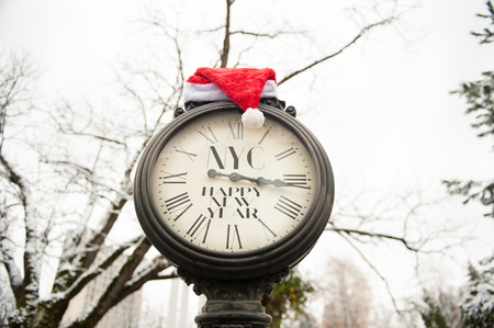 vintage street clock with inscription Happy New Year NYC and Santa Claus hat on them outdoors in winter