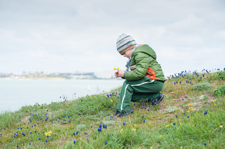 little child in jacket and hat collecting spring flowers on green slope against backdrop of sea