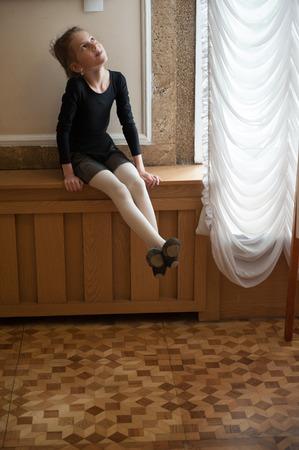Little girl in ballerina costume sits on the windowsill dreaming