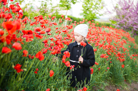 Cute little girl in a coat and hat collects poppies on a flowering field
