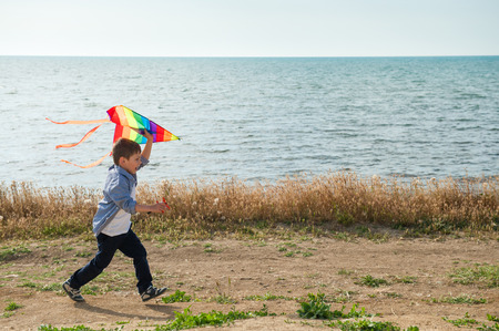 active happy kid running with colourful kite in his hands along sea shore Stock Photo
