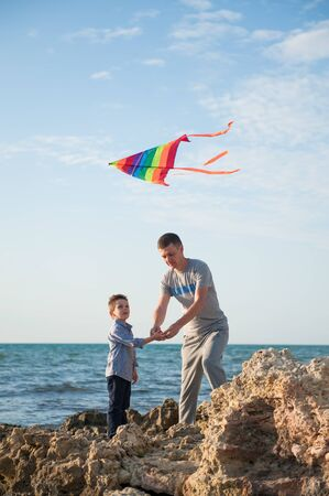 father and little son launch a kite by the sea and blue sky Stok Fotoğraf