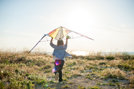 little boy run across the grass field with a kite in his hands