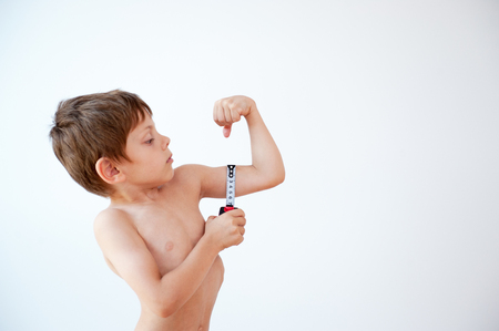 little boy measures his muscles with a measuring tape