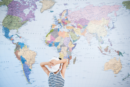 small boy in the hat of captain looking at world map, clutching his head