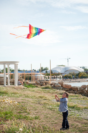 happy little boy holds a flying kite in the air against the sea coast