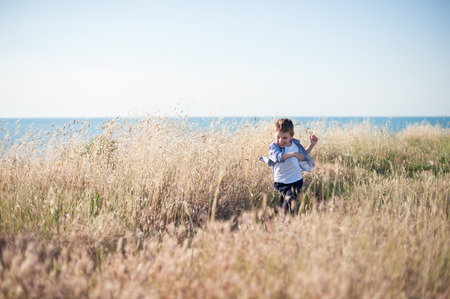 free little boy running across field of dried grass on sea background 版權商用圖片