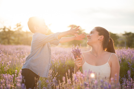 happy cute little boy wants to hug mother and reaches out to her with open arms among flower fields in summer