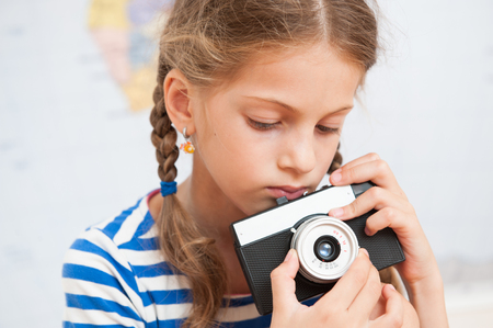 portrait of cute little girl holding a vintage film camera Stock Photo