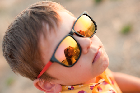 cute little boy with sunglasses that reflect beautiful small girl in summer evening Stock Photo