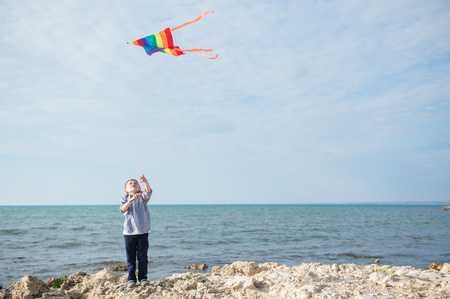 little boy holding kite soaring in sky against background of open sea