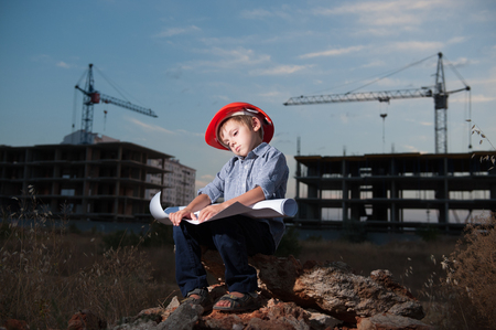 tired boy wearing helmet solves problem of project on construction site with building crane in the background at end of day