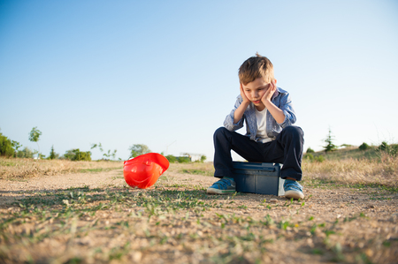 sad little kid sitting on box with tools and helmet lying next to him lose job Stock Photo