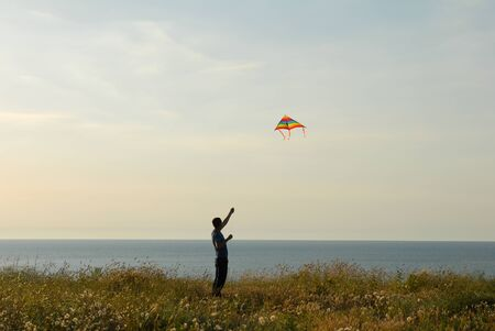 active young man launches colorful kite on sea coast at sunset in summer Imagens