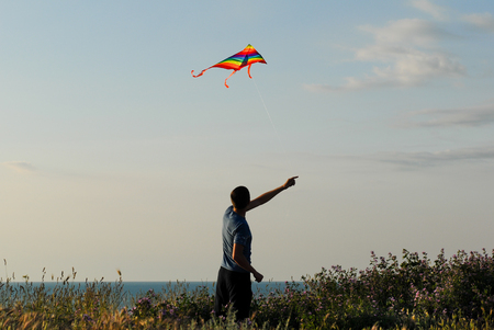 active young man controls colorful kite floating in air at sunset near sea shore Banque d'images