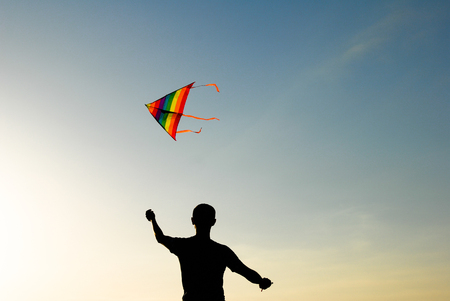 silhouette of active young man controlling colorful kite flying in air at sunset
