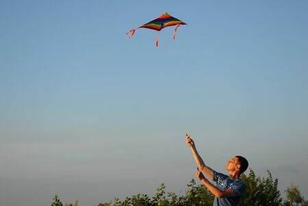 active young man controlling colorful kite flying in air at summer sunset