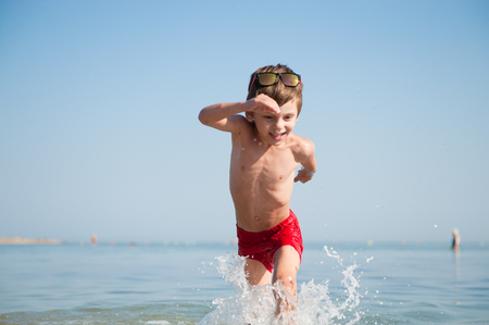 active happy little kid wearing sunglasses and red shorts running in sea water with splashes in summer holiday Reklamní fotografie