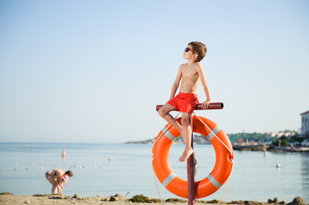 healthy little boy in sunglasses sits on pole with orange lifebuoy hanging on it on summer beach with people