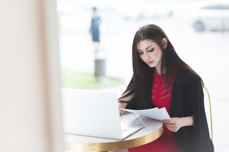 smart business girl sitting in cafe and studying documents sitting by laptop