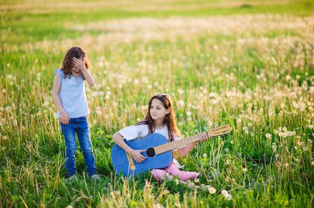 two cute little girls standing in the summer field playing guitar and having fun outdoors in summer