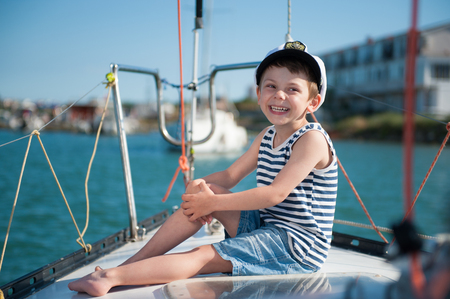 handsome laughing happy kid in captain hat sitting on luxury yacht in summer sunny day