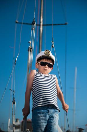 cute kid in captain hat on board of boat in summer