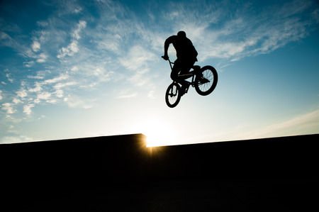 silhouette of jumping biker on summer sunset with copy space Stock fotó