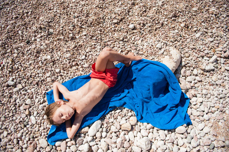 healthy little boy in red shorts lying on blue towel on beach in hot summer day
