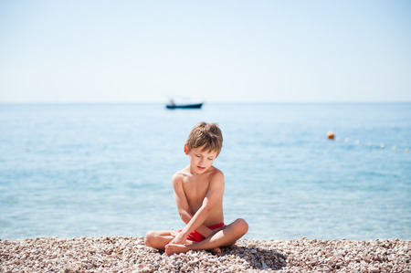 handsome small caucasian kid sitting on sea shore beach with sea horizon with boat behind Stock Photo