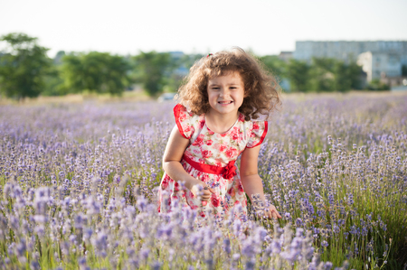 funny handsome little girl with clenched teeth bouquet of flowers in field Stock Photo