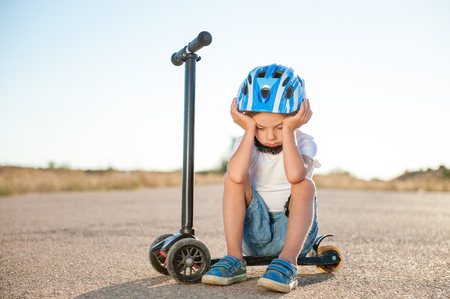 sad tired little boy in sport helmet sitting on scooter on road head down Stockfoto