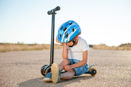 sad tired injured little boy in blue sport helmet sitting on scooter on road head down Фото со стока