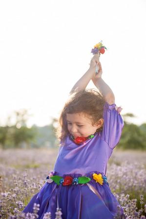 grappig schattig klein meisje in sprookjesjurk en magische stok in de zomer Lavendel veld buiten