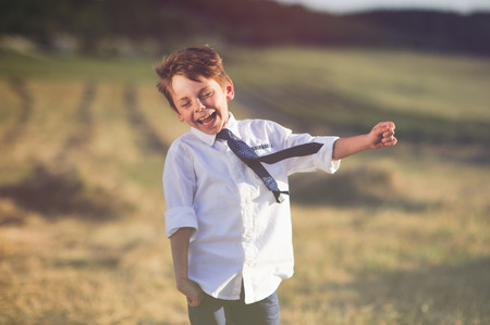 funny laughing little boy wearing white shirt and tie fluttering on blowing wind outdoor
