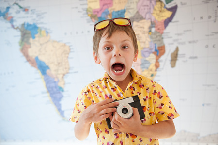 funny shouting little kid in yellow shirt with vintage camera in hands on world map backdrop