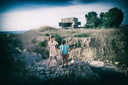 crying caucasian little girl and sad boy on ruins of their house destroyed in civil war