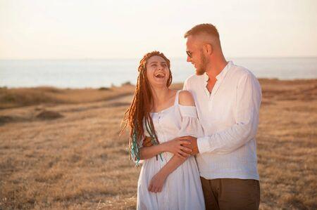 cute boyfriend in sunglasses embracing girlfriend with dreadlocks on sea shore in summer