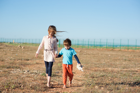 two kids migrants walking in desert shoeless with plush toy along state border fencing Foto de archivo