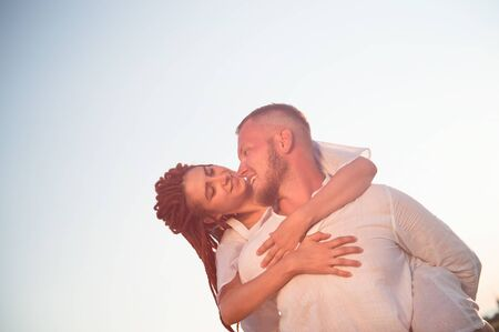 happy smiling young caucasian couple man and woman on summer warm sunset love each other