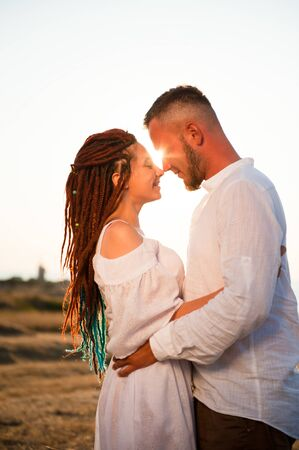 beautiful happy young woman with dreadlocks hugging bearded cute man on summer sunset Stok Fotoğraf