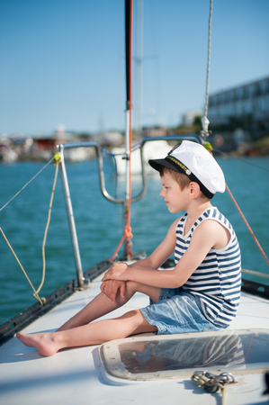 pensive small caucasian boy in captain hat sitting luxury yacht board watching far ahead