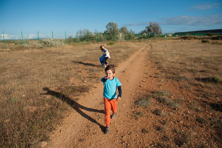 little boy and girl refugees in desert near state border with fencing in hot summer