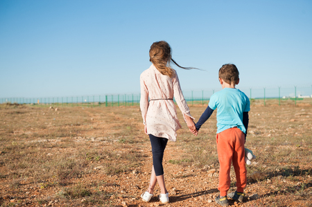 small brother and sister refugees holding hands standing among desert on state border Stockfoto