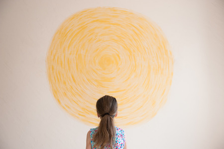 little girl looking at yellow sun painted on wall Stock Photo