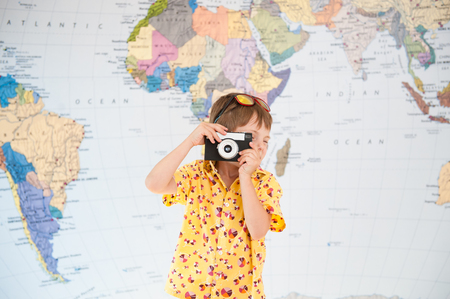 little caucasian boy taking picture with vintage film camera on world map background Stock Photo