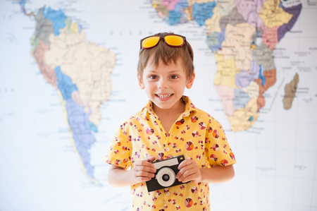 happy smiling caucasian little boy with vintage camera in hands on world map background